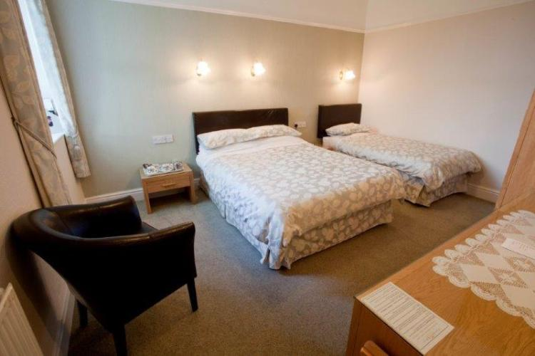 A spacious room with a double and single bed