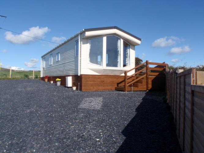Driveway with ample parking space and steps leading up to the decking area and garden