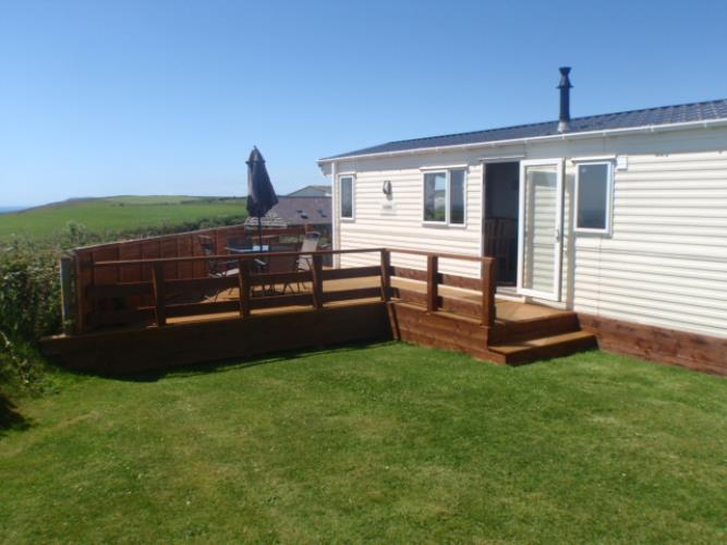 Garden & decking area with far reaching views of the sea and the surrounding landscape